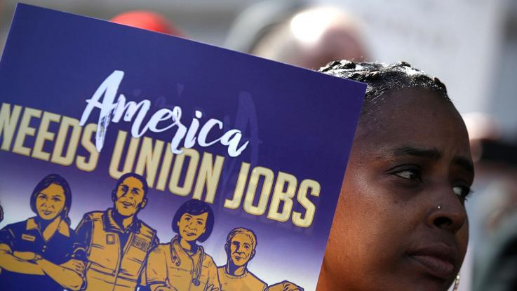 African-American woman holding an America Needs Union Jobs picket sign