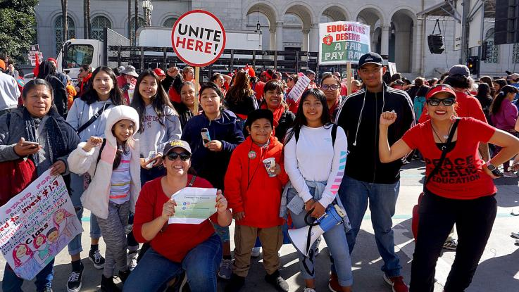 Adrian De La Cruz, second from right in black and white striped jacket, stands with other supporters in front of LA City Hall during UTLA's teachers' strike in January 2019.