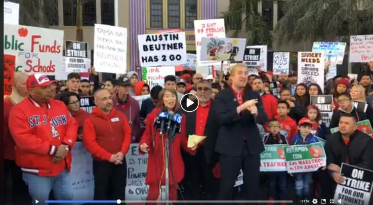 Photo of UTLA's Morning Press Conference at Bell HS. Arlene Inouye and sign language interpreter along with teachers in the background. This is a Facebook Live video to click on.