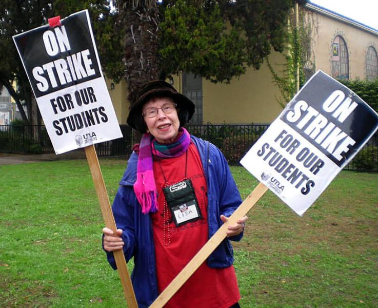 Retired teacher and UTLA member Lisa Edmondson stands with a smile holding picket signs outside Palms ES during the Los Angeles teachers' strike in January 2019.